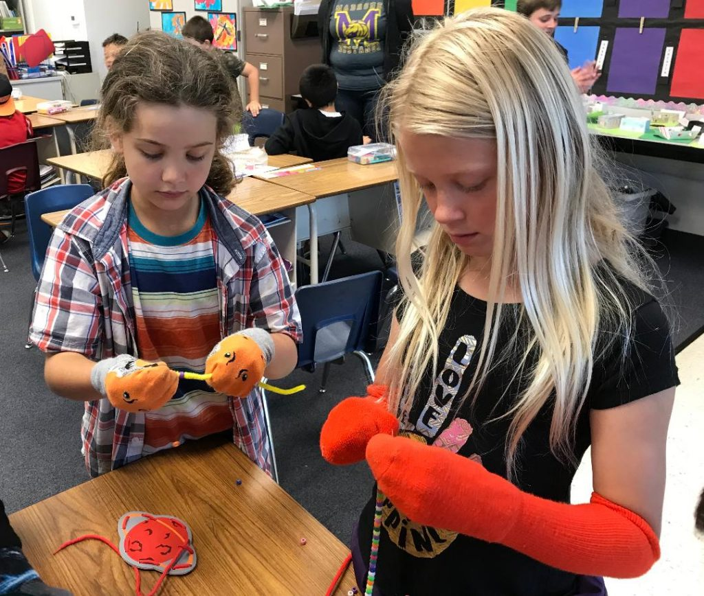Picture of two girls beading with socks on their hands